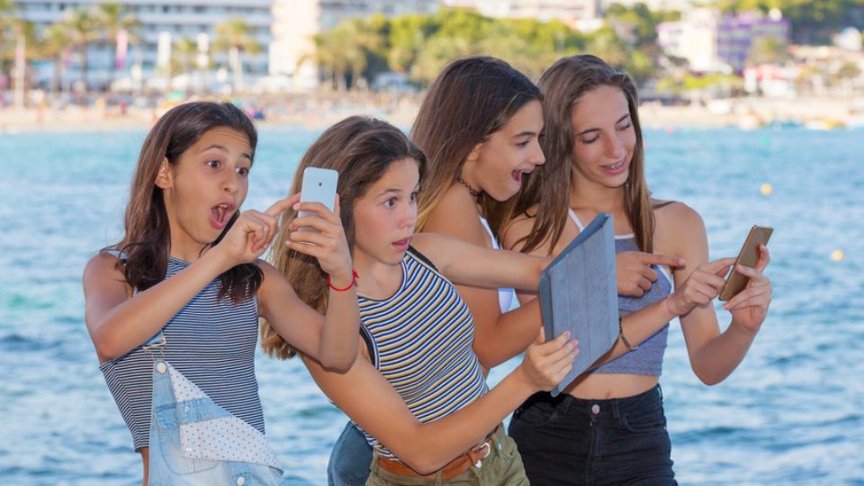 Children hunting Pokemon Go playing with app on mobile phones